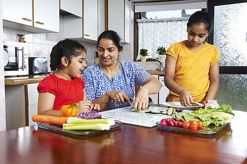 Mother and two daughters preparing a meal together